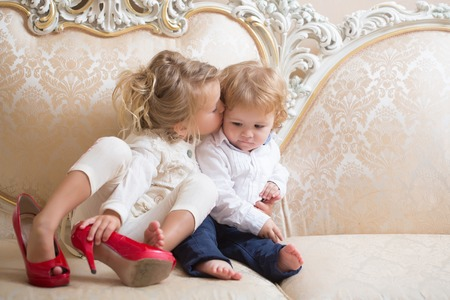 Sister kiss brother with blond hair on classic sofa