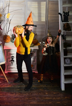 Small girl and father celebrate halloween. Father and small girl enjoy halloween. Man and child have halloween celebration. Man hold carved pumpkin. Have chills and thrills on Halloween 스톡 콘텐츠