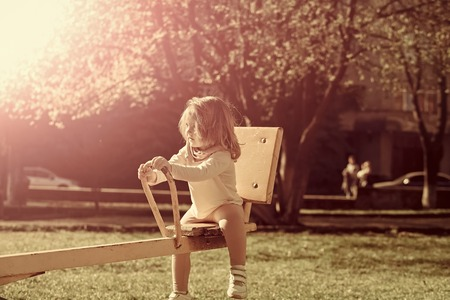 Girl sit on seesaw on sunny day Stockfoto