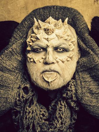 Man with dragon skin and beard Stock Photo
