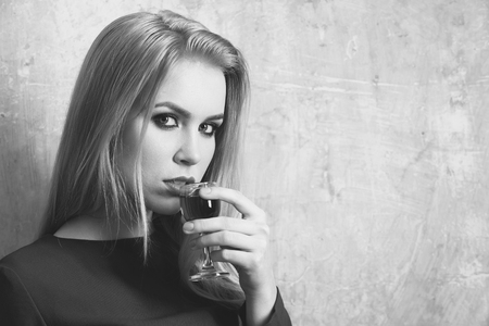 Woman drinking red liqueur in glass