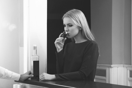 Woman drinking glass of wine at bar