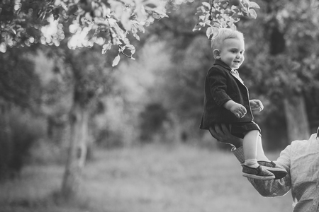 Cute toddler smile in suit, shirts, sneakers under tree, fashion