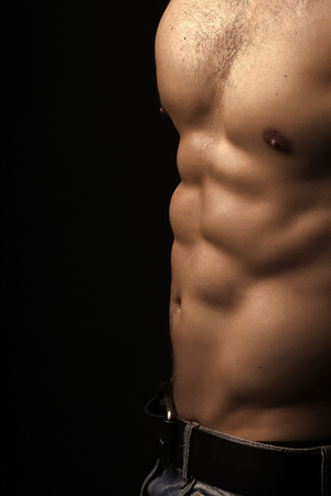 Closeup view of one handsome strong young male chest of muscular body standing posing on studio background, vertical picture