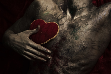 Nude torso with red plush soft heart toy, dark background. Valentines day concept. Male chest covered with shimmering silver paint and colorful glitters. Depression, loneliness, love, sadness.