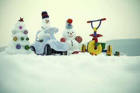 Snowmen and snow xmas tree on white sky. Tricycle and toy car on snowy background. Festive surprise and presents. Christmas and new year. Winter holidays celebration concept.