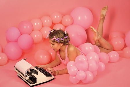 Education and childhood. Child in underwear with typewriter on pink background. Kid journalist or writer, career. Little girl secretary at party balloons. Small girl with curler in hair typing. Banco de Imagens