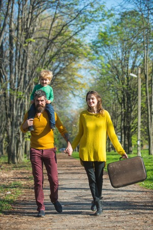 Leisure travelers of husband and wife with little son walk on park road. Traveler attraction. Take your bag and leave today