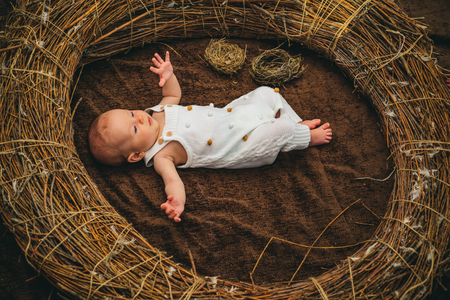 Happy newborn child awake in crib. Newborn girl or boy. Happy birth day. Registering birth and other vital event. Birth is event in child life, not her or his beginning. Your child future begins here