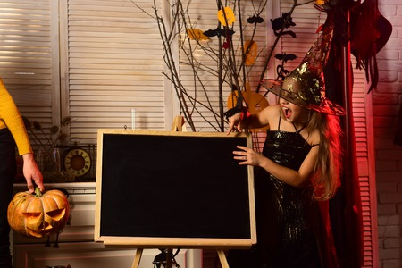 Happy small child envite to halloween party. Small girl dressed for costume party pointing at blackboard. Happy halloween, witches. I got a feeling that tonight is gonna be a boo night, copy space Banco de Imagens