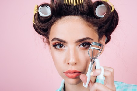 beauty salon hairdresser. retro woman with fashion makeup and hair. vintage housewife woman curl eyelash with tool. Pinup girl. happy girl grooming in morning. Loving her new style. Feeling flirty Banque d'images