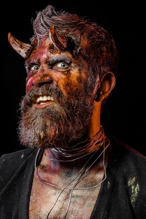 Halloween demon grin teeth with bloody horns on head