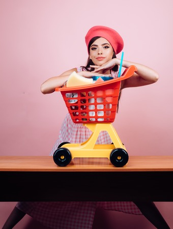 savings on purchases. vintage housewife woman ready to pay in supermarket. happy girl enjoying online shopping. retro french woman go shopping with full cart. online shopping app. I have done it Stock Photo