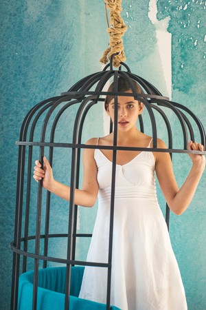 fashion slave in captivity of beauty. freedom of cute girl in cage chair. modern furniture design and home comfort. woman in iron cage. prisoner woman in cage - home confinement. Beautiful female