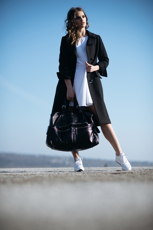 Beauty and fashion look. Pretty girl with fashionable hair. autumn fashion of business woman with bag. Fashion woman with stylish makeup and curly hair. Feeling flirty. Gorgeous and beautiful