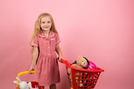 Shopping is a bit of a relaxing hobby for me. Little girl shopping. Little shopaholic with shopping cart. Small girl in shop. Small shopper. Kind of girl restyled in a retro way