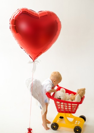 little boy go shopping with full cart. little boy child in toy shop. valentines day and love. shopping for children. happy childhood and care. savings on purchases. Why not. Friendly shop assistant