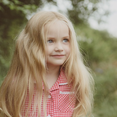 Hair care. Happy little child with adorable smile. Little girl wear long hair. Small girl with blond hair. Small child happy smiling. The secret of a happy childhood Stock Photo