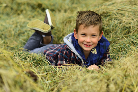 Agriculture is in my heart. Little boy relax in hayloft. Little boy enjoy free time in countryside. Go organic and natural. Bring diversity back to agriculture