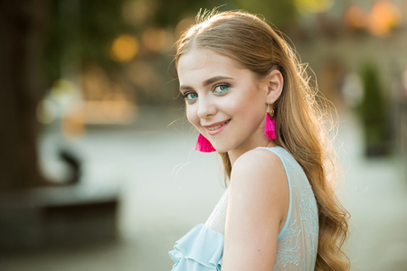Beauty and fashion look of model. happy woman with stylish makeup and long blonde hair. summer fashion woman. Fashion is her life. Pretty girl with fashionable hair and pink earrings. Perfect female
