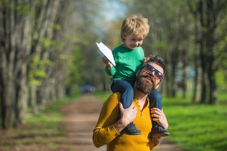 Traveling by plane. Small child boy on fathers shoulder launch paper plane in park, traveling concept. Flying better than ever