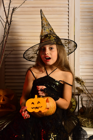 Small girl do magic on halloween. Small girl in witch hat with pumpkin. I put a spell on you. Magic factory is here