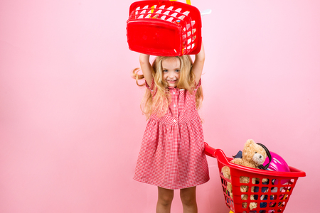 I always say shopping is cheaper than a psychiatrist. Happy little girl shopping. Little shopaholic with shopping cart. Foto de archivo - 109839395
