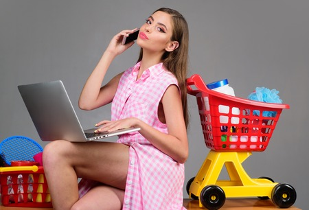 Making the retail connection. saving on purchase. retro woman go shopping with full cart. vintage housewife woman ready to pay in supermarket. happy girl enjoying online shopping. Stock Photo