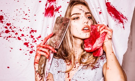 Scary woman with blood on face holding a rusty and bloody cleaver and meat in front of her face. Sexy girl dress killer to Halloween festival. Fear and horror. Steak concept. Фото со стока