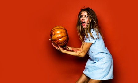 Halloween sexy student girl in blood with pumpkin. Dirty in blood, woman holds in hands bloody pumpkin on red background in studio.