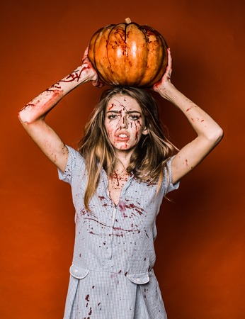 Halloween girl with a carved Pumpkin. Portrait of a woman with make up blood on her face. Sexy woman wear blue drees with blood. She has pumpkin holds in hands over head.