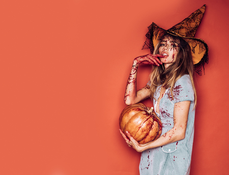 Halloween girl with a carved Pumpkin. Beautiful young surprised woman in costume holding pumpkin. Halloween Witch with pumpkin. Sexy vampire woman with blood on her face. Halloween party art design.