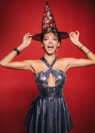 Beautiful young surprised woman in witches hat. Pretty young blonde woman dressed as fairy. Elegant charming shy playful dangerous mysterious scary female beauty.