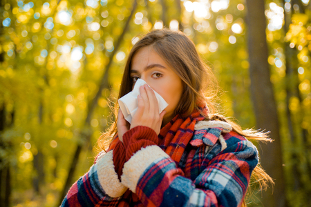 Woman with napkin sneezing in the yellow park. Sick people has runny nose. Allergy season. Woman makes a cure for the common cold. Woman makes a cure for the common cold in autumn park.