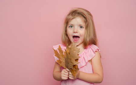 Kid having fun with Leaf fall. Fashion portrait of beautiful sensual little pretty girl. Having fun. Portrait of beautiful cute girl with blonde hair. Autumn time.