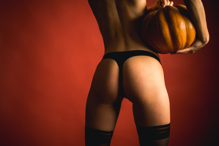 The Most Popular Candy for Halloween. Halloween poster with pumpkins. Pumpkin with sexy ass. Stock Photo