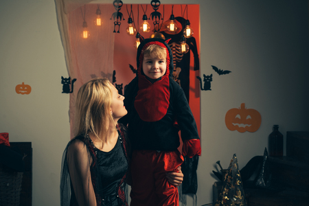 Family fun mother and child son having fun and celebrate Halloween in devil costume. Beautiful young woman with a child with pumpkins autumn.