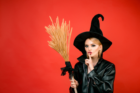 Witch holding broom or broomstick. secret Halloween. Young women in black witch halloween costumes on party over red background.