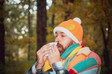 Mature man in jacket suffering from cold. Blowing nose with a tissue, looking miserable unwell very sick.