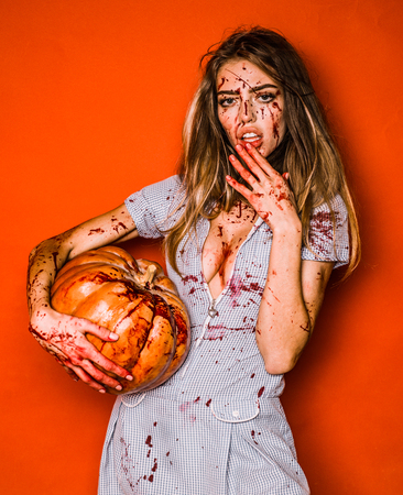 Beautiful Young woman as sexy vampire - halloween concept. Scary bloody zombie girl with pumpkin. Woman with red blood and with blond hair.
