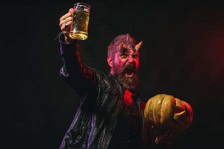Halloween man with satan horns hold pumpkin Zdjęcie Seryjne