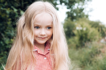Hair is important part of her look. Small girl with blond hair. Happy little child with adorable smile.