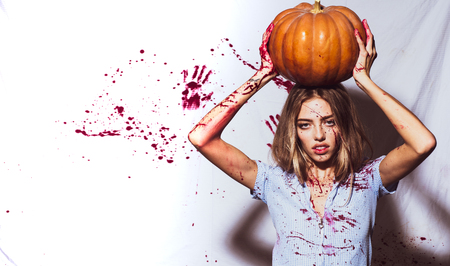 Sexy girl murderers hold pumpkin in her head. Halloween sexy student girl in blood with pumpkin. Halloween theme. Wide banner with halloween pumpkin and bloody girl.