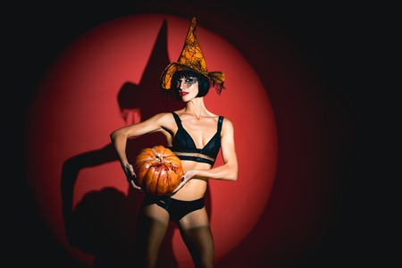 Sexy stripper Woman with pumpkins. vampire girls. Sunsual desire concept. Halloween lingerie model. Imagens