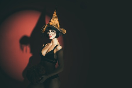 Sexy stripper Woman with pumpkins. Halloween lingerie model. Vampire girls. Sunsual desire concept. 免版税图像