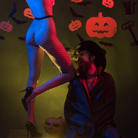 Woman shows a beautiful or butt. Night Party background. Sexy Horror background. Holiday halloween with funny carnival costumes on a halloween background. Romantic couple. Happy halloween.