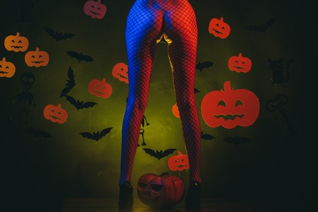Autumn time for Fashion sale. Secrets of Magic for Happy Halloween. Sexy buttocks. Halloween poster with pumpkins. Female with posing on pumpkin.