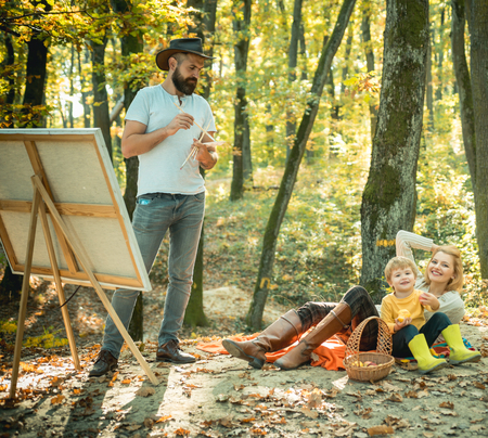 Autumn garden party - Father, mather and son. Camping with kids. Enjoying good weather. Man artist painting autumn picture. Фото со стока