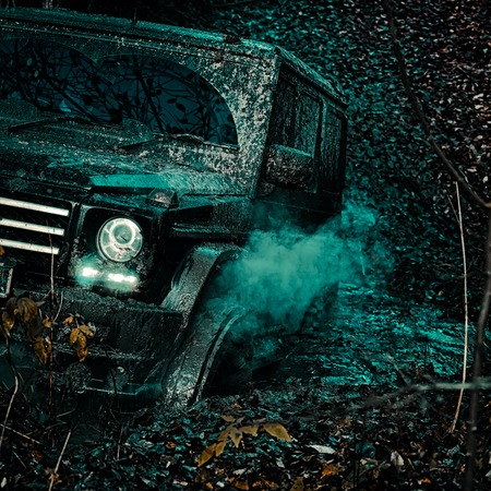 Offroad vehicle coming out of a mud hole hazard. Road adventure. Adventure travel. Mudding is off-roading through an area of wet mud or clay. Travel concept with big 4x4 car.