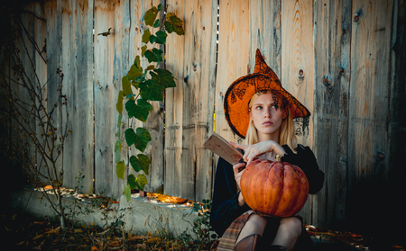 Portrait of women in halloween costumes over outdoor wood background. Concept of Halloween. Close-up portrait of gorgeous blonde fairy. Stock Photo
